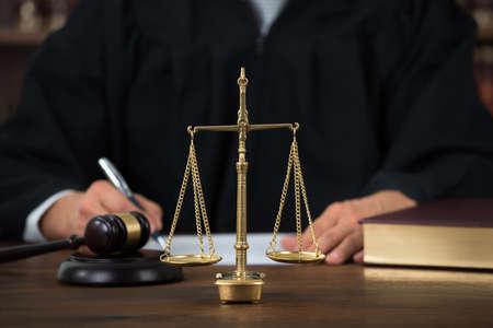 Wet schalen op tafel met de rechter schriftelijk op de achtergrond in rechtszaal