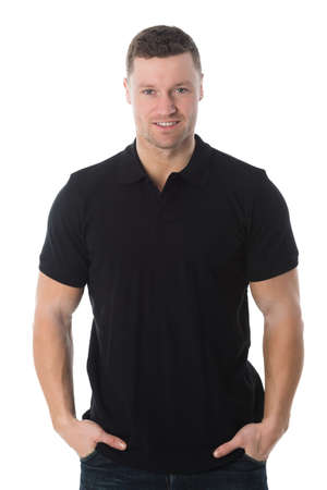 Handsome mid adult man in black tshirt standing with hands in pockets against white background Stock Photo