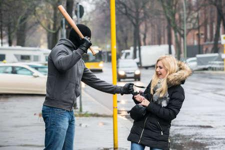 delito: Ladrón Mujer golpear con el bate de béisbol, mientras que tratando de robar el bolso en la acera durante el invierno