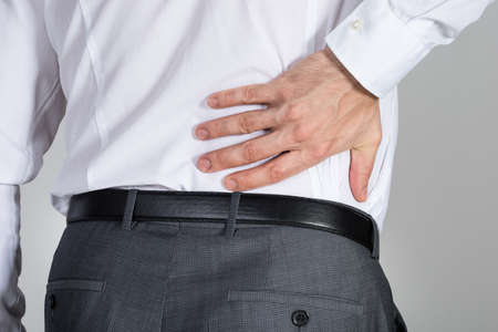 back view of man: Rear view of businessman suffering from back ache against white background
