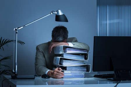 agotado: hombre de negocios agotado la cabeza apoyada en las carpetas, mientras que trabajar hasta tarde en la oficina