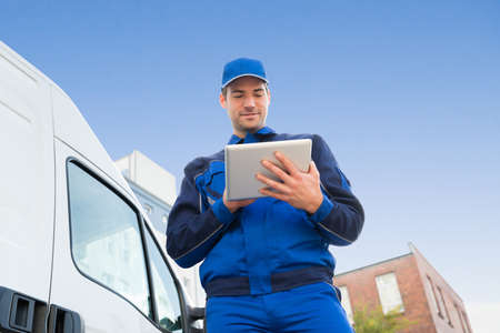 moving truck: Low angle view of delivery man using digital tablet by truck against sky