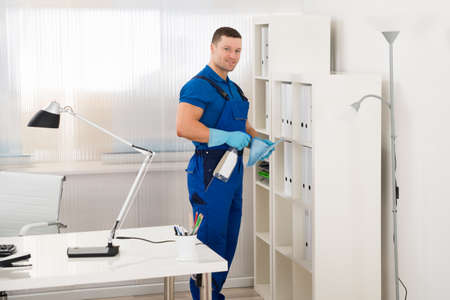 work gloves: Mid adult male worker cleaning shelf with spray and sponge at office Stock Photo