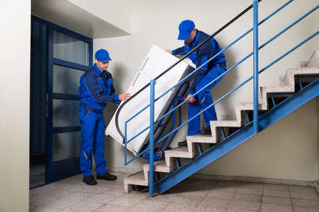 Full length of male movers carrying refrigerator while climbing steps at home Imagens