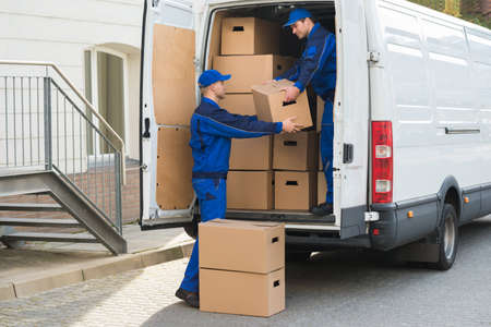 people moving: Young delivery men unloading cardboard boxes from truck