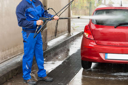 washing car: Mature serviceman with high pressure water jet washing red car at service station