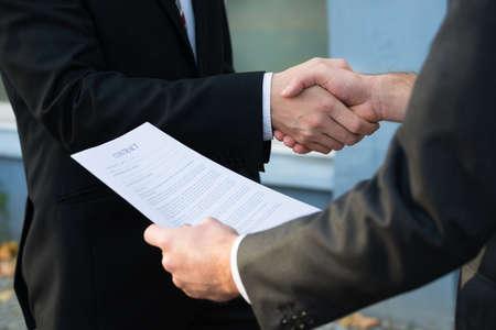Imagen recortada de hombre de negocios dándose la mano con su pareja mientras mantiene documentos de contrato Foto de archivo