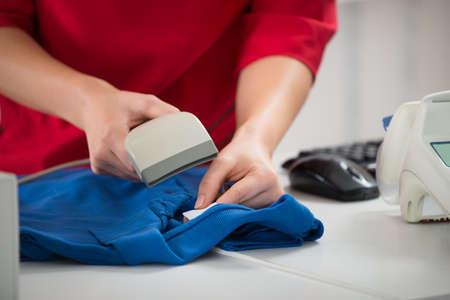 codigos de barra: Sección media de la exploración del código de barras en la camiseta vendedora en el mostrador