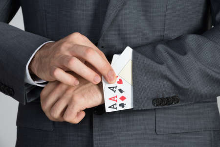 cheat: Midsection of businessman removing ace cards from sleeve in office