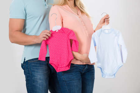 eagerness: Midsection of couple holding baby clothing over white background