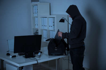 thievery: Male burglar putting laptop into bag at desk in office at night Stock Photo