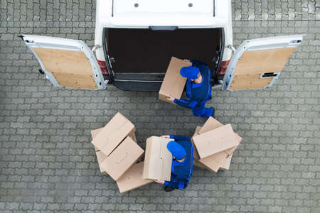 Directly above shot of delivery men unloading cardboard boxes from truck on street Stockfoto