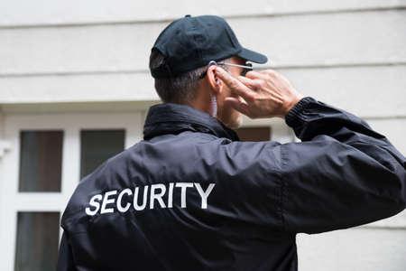 Achteraanzicht van volwassen bewaker luisteren naar oortelefoon tegen gebouw