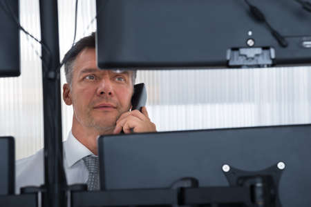 stock trader: Mature male stock trader using telephone while looking at multiple computer screens at office