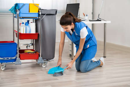 Full length of young female cleaner sweeping wooden floor in office Banque d'images