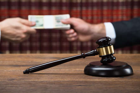 Gavel on wooden table with judge taking bribe from businessman in background at courtroom Stock Photo