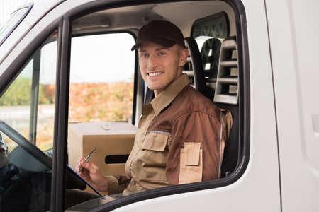 cajas de carton: Portrait of confident delivery man making checklist in truck
