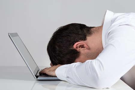 hombres trabajando: Vista lateral de empresario hizo hincapié en que se inclina en la computadora portátil en el escritorio contra el fondo blanco