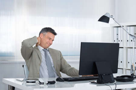 hands massage: Mature businessman suffering from neck pain at desk in office