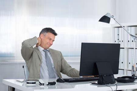 Zralé podnikatel trpí bolestí krku u stolu v kanceláři