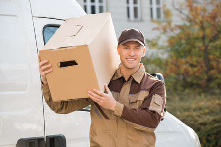 distribution box: Portrait of young delivery man carrying cardboard box on shoulder with truck in background