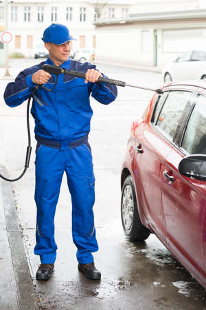 serviceman: Confident serviceman with high pressure water jet washing car at service station