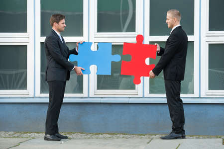 jigsaw pieces: Side view of businessmen joining jigsaw pieces while standing outside office