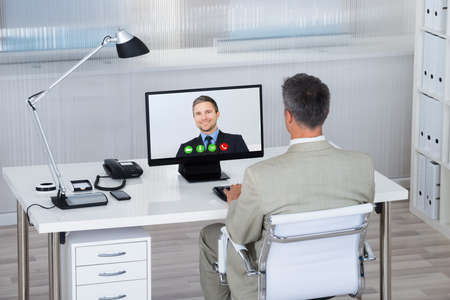 conferencing: Rear view of businessman video conferencing with partner on computer at desk in office Stock Photo