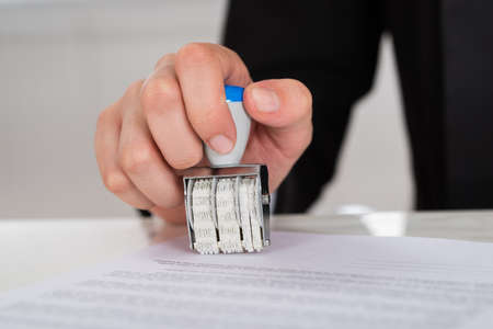 signing authority: Cropped image of young businesswoman stamping contract paper at office desk