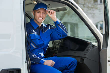 protective workwear: Portrait of happy technician in protective workwear sitting inside van