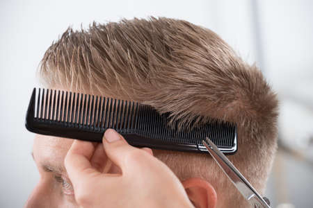 comb hair: Young man getting haircut from female hairdresser at salon