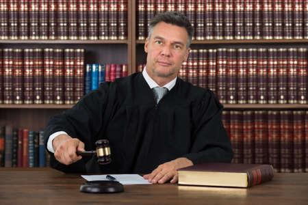 orden judicial: Seguros de juez de sexo masculino maduro golpear el martillo en la mesa contra el estante