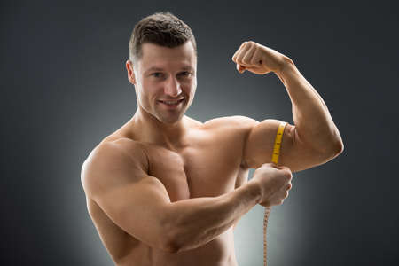 Portrait of happy muscular man measuring bicep with measure tape against black background