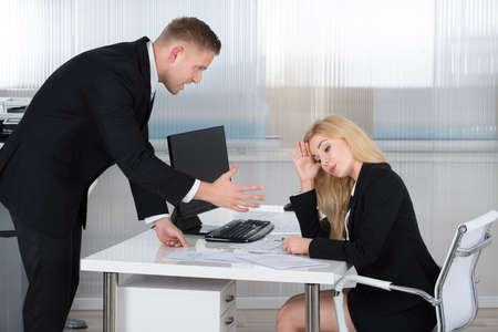 bully: Boss shouting at female employee sitting at desk in office Stock Photo