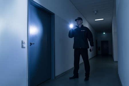 성숙한 보안 경비원의 전체 길이 건물 앞에 문 앞에 손전등 서