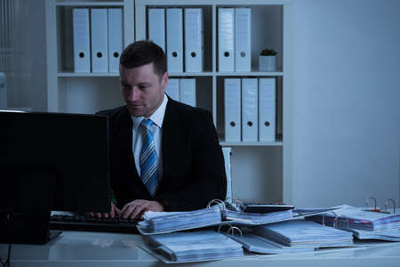 late 30s: Mid adult businessman using desktop PC while working late in office