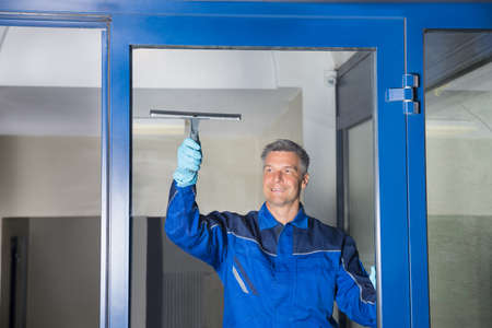 window cleaning: Happy mature male worker cleaning glass with squeegee Stock Photo
