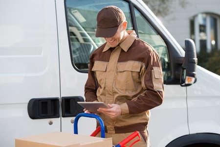 Portrait of smiling delivery man holding digital tablet against truck