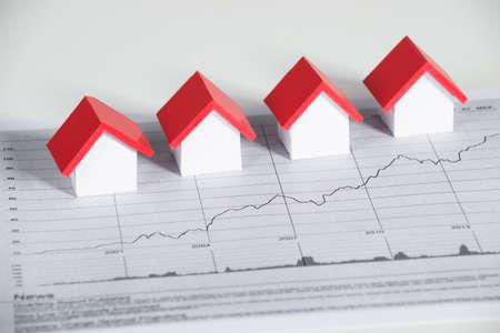 Erhöhte Ansicht von Hausmodelle auf Finanzdiagramm am Schreibtisch Standard-Bild
