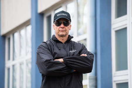 Portrait of confident mature security guard standing arms crossed outside building