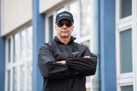 Ritratto di fiducioso guardia di sicurezza maturo in piedi braccia incrociate edificio esterno