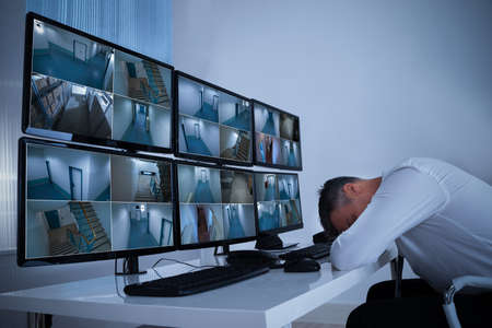Side view of mature male operator sleeping while leaning on security monitors desk in office