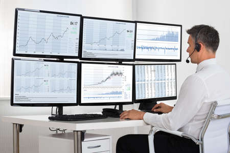 trader: Side view of stock market broker looking at graphs on multiple screens in office