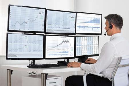 agente comercial: Vista lateral del corredor de bolsa mirando gráficos en múltiples pantallas en la oficina