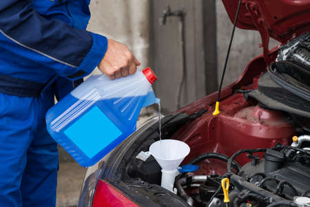 serviceman: Cropped image of mature serviceman pouring windshield washer fluid into car at service station