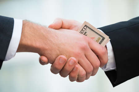 bribing: Cropped image of businessman bribing partner while shaking hand outdoors