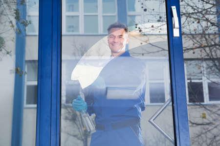 uniformes de oficina: Retrato de feliz trabajador de limpieza de vidrio macho maduro con un trapo Foto de archivo