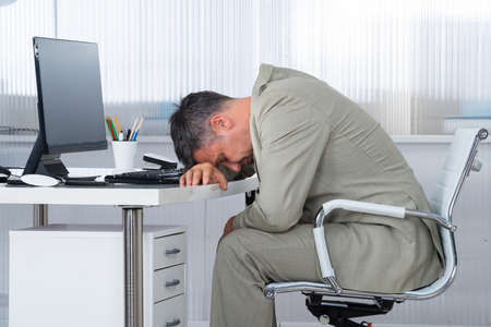 asleep chair: Side view of tired businessman sleeping on desk in office