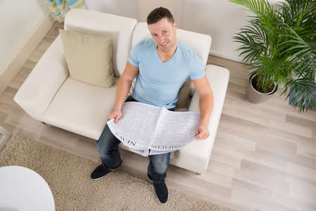 mid thirties: High angle view of mid adult man reading newspaper on sofa at home