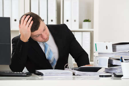 hands on head: Stressed male accountant sitting with head in hand at desk in office